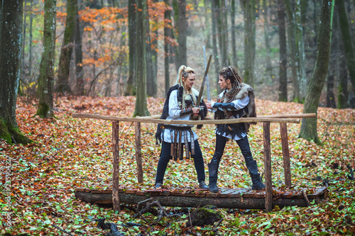 2 (two) dangerous scandinavian viking women warriors fighting with swords on footbridge in forest Canvas Print