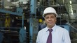 Tilt down of middle aged Latin American manager in hardhat standing with clipboard in factory, looking at camera and smiling