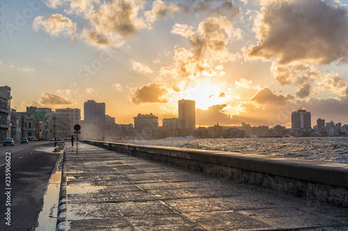 Fotobehang Havana Havanna Malecón mit Welle bei Sonnenaufgang