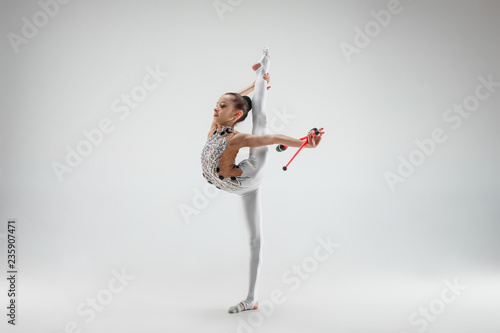 Valokuva  The teen female little girl doing gymnastics exercises with clubs isolated on a gray studio background