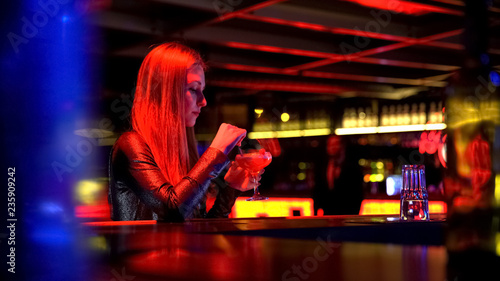 Beautiful young woman sitting and drinking cocktail at party in nightclub - 235909242