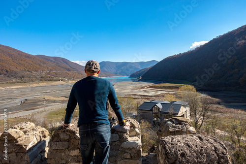Foto op Plexiglas Aziatische Plekken A man standing at the edge of the fortress looks at a mountain valley