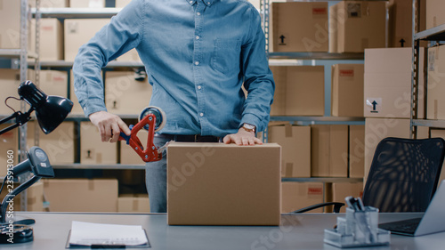Foto Professional Warehouse Worker Checks and Seales Cardboard Box Ready for Shipment