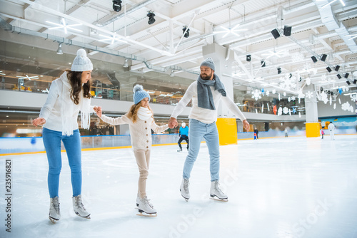 Fotografia happy family holding hands while skating together on ice rink