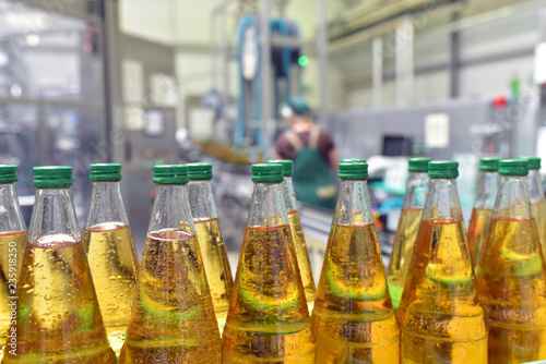 Fotomural  apple juice in glass bottles in a factory for the food industry - bottling and t