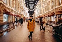 Pretty Woman In Yellow Coat And Glasses Is Standing Near Shopping Mall GUM Illuminated At Night. Moscow, Russia