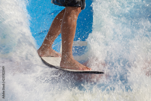 Fotografie, Obraz  Man take wake surf, riding a surfboard or foot board along an outdoor water slid