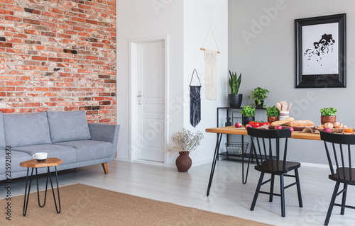 Grey Sofa Against Red Brick Wall In Flat Interior With Poster And Black Chairs At Dining Table Real Photo Buy This Stock Photo And Explore Similar Images At Adobe Stock