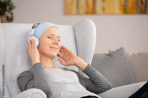 Foto  Peaceful woman with headphones and blue headscarf resting at home after cancer t