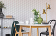 Leinwanddruck Bild - Black and white chair at wooden table in dining room interior with flowers and gold lamp. Real photo