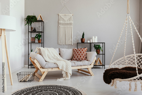 Photo Handmade macrame on the empty wall of bright beige living room with comfortable