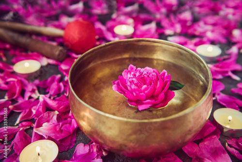Fototapeta Tibetan singing bowl with floating inside in water purple peony flower