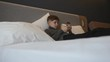 The boy is lying on the bed with a smartphone in his hands. Communication and games on the smartphone
