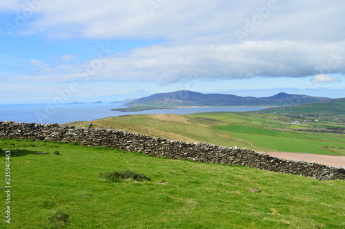 Typical Irish green landscape with coastline and small wall