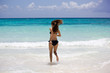 Junge sportliche Frau rennt in das Karibische Meer