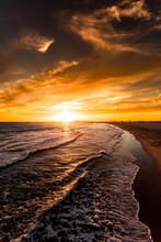 Waves Crashing On A Beach During Sunset