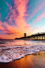 Colorful Clouds As Waves Crash On The Beach During Sunset