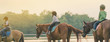 Kids learn to ride a horse near the river before sunset.