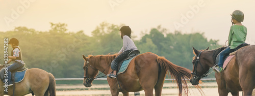 Foto op Canvas Paarden Kids learn to ride a horse near the river before sunset.