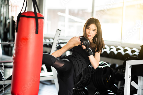 Fotomural  Attractive female boxer training with kick boxing at gym with blackgloves