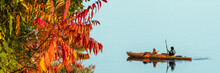 Colorful Leaves And Two People In A Kayak In The Background