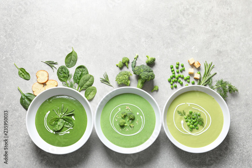 Dishes with different fresh vegetable detox soups made of green peas, broccoli, spinach and ingredients on table, flat lay