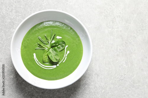 Fresh vegetable detox soup made of spinach in dish and space for text on table, top view