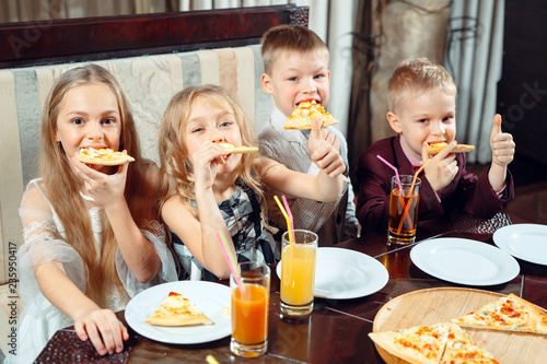 Children eat pizza in the restaurant.