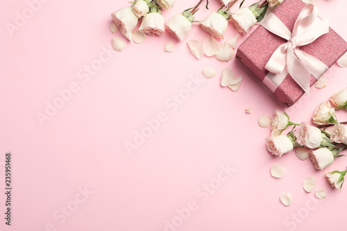 Flat lay composition with beautiful roses and gift box on color background. Space for text
