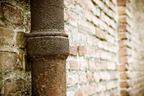 Valokuva  Detail of a downpipe against a brick wall - (Tuscany - Italy)