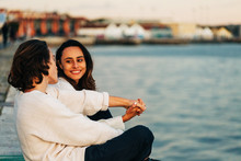Young Man And Woman Sitting On Embankment Near Water