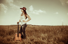 Gorgeous Cowgirl With Old Guitar Standing At Rural Meadow