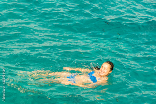 Foto auf AluDibond Tauchen Young woman smiles, swiming in ocean. Young woman in bikini swimming in clear water.