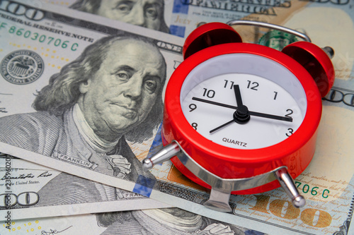concept of time value. Cool alarm clock on US dollars. Fototapet