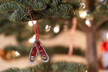 Holiday Decorations, Ornament On A Authentic Christmas Tree, With Candy Cane And Snow Shoe Hanging From Tree With Lights In The Background