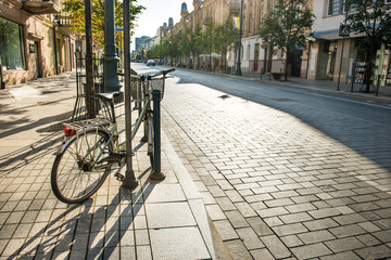 Bike on city street with empty road and morning light in Europe, Lithuania, Vilnius