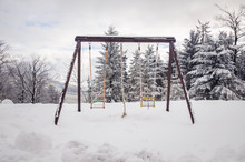 Empty Playground In Wintertime Near Forest