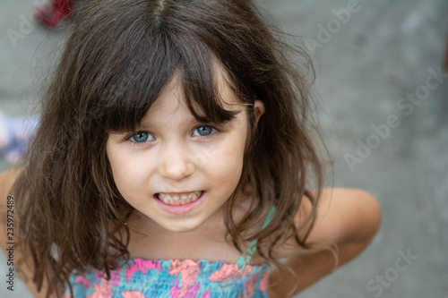 Portrait Of A Beautiful Young Brunette Little Girl Curly Hair Blue Eyes Wearing A Summer Dress 4 Or 5 Years Old