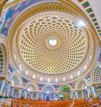 MOSTA, MALTA - JUNE 14, 2018: Interior Of Huge Basilica Of The Assumption Of Our Lady (Rotunda) With Richly Decorated Arched Niches, Beautiful Altar And Impressive Dome, On June 14 In Mosta.