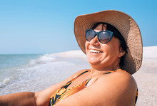 Happy Smiling Elderly Womanr Woman In Sunglasses And Big Hat Takes Sun Bath On Seaside