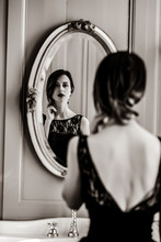 Portrait Of Beautiful Young Woman Looking At Herself In The Wonderful Mirror . Image In Black And White Color Style