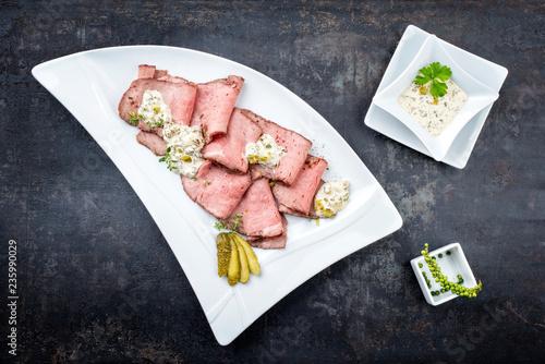 Traditionelles bayrischer Brotzeit Aufschnitt mit Rostbraten Scheiben und Remoulade als Draufsicht auf einem weißen Modern Design Teller auf schwarzen Hintergrund