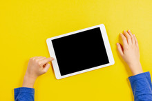 Kid Hands With Tablet Computer On Yellow Background