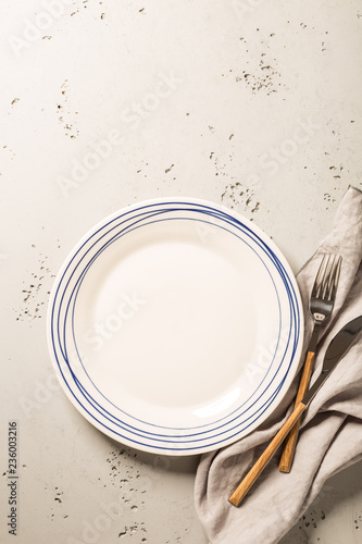 Empty white plate, napkin and cutlery on grey stone background