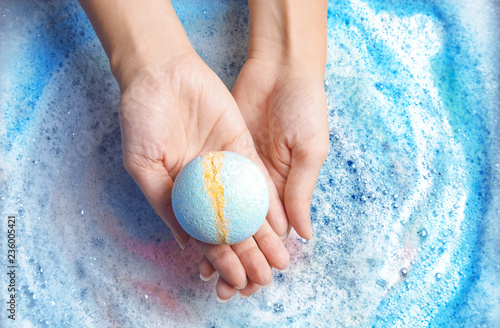 Canvas Print Woman holding color bath bomb over foam, top view