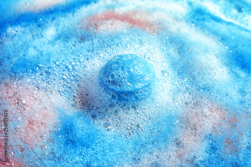 Fényképezés Dissolving color bath bomb in water, closeup