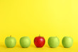 Row of green apples with red one on color background. Be different