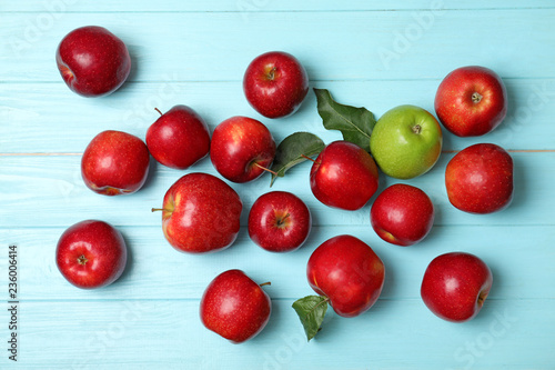 Obraz Green apple among red ones on wooden background, top view. Be different - fototapety do salonu