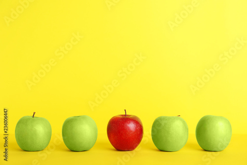 Obraz Row of green apples with red one on color background. Be different - fototapety do salonu