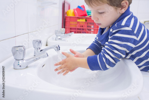 Child boy washing hands at adapted school sink Canvas Print